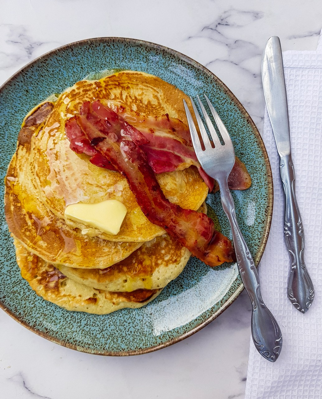Fluffy American style pancake with bacon and maple syrup
